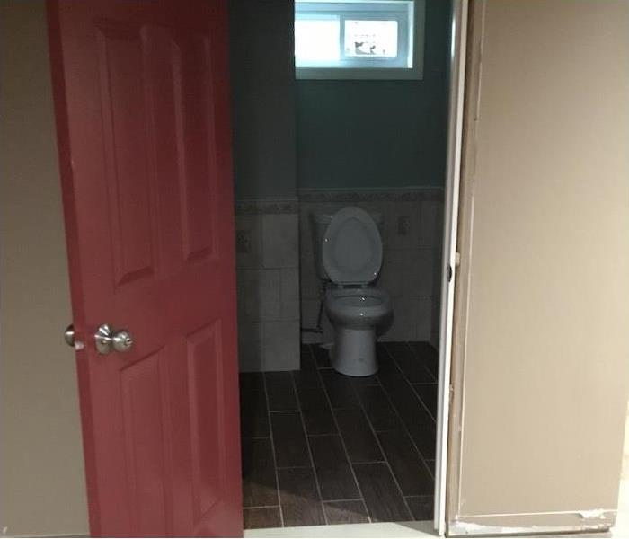 bathroom cleaned with tile floor and red door