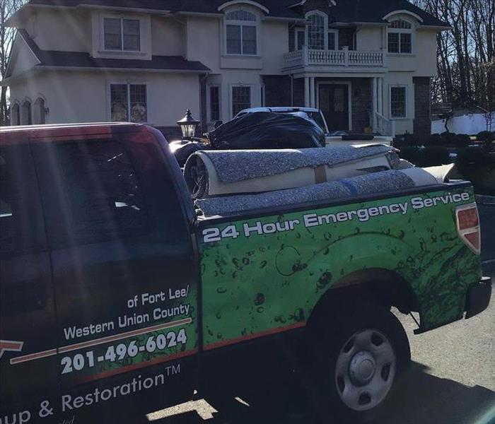A SERVPRO truck in front of a home, with damaged materials in the truck bed.