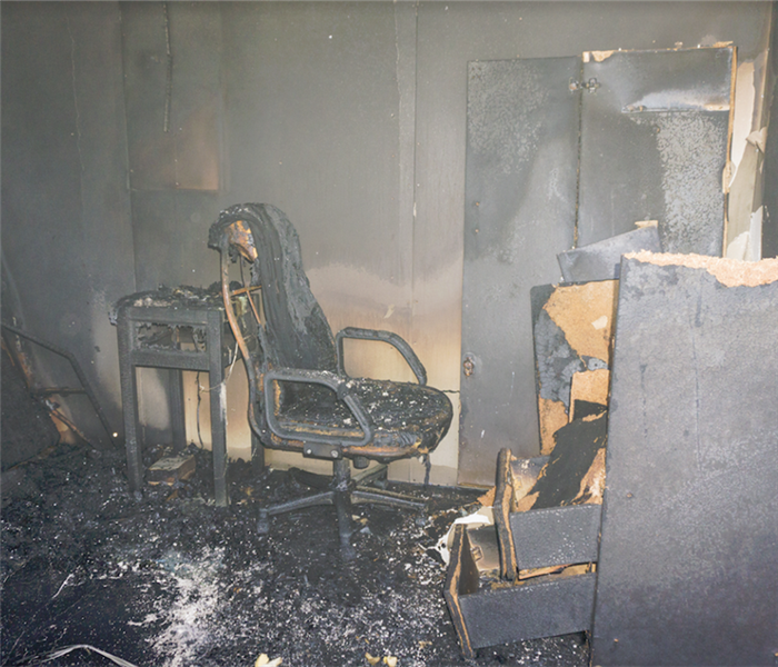 a fire damaged room with soot covering everything and charred debris everywhere